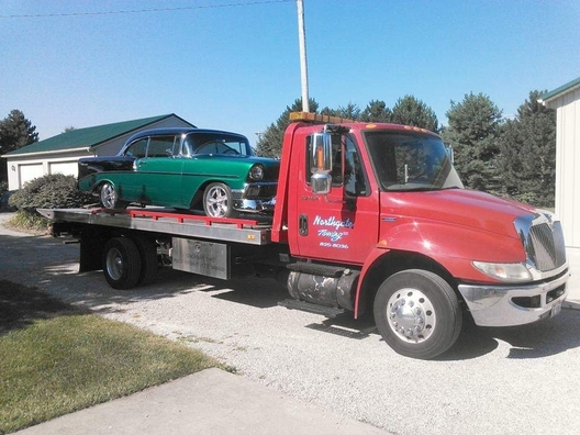 Picture of our red flatbed truck towing a green car for a customer in Cincinnati, OH